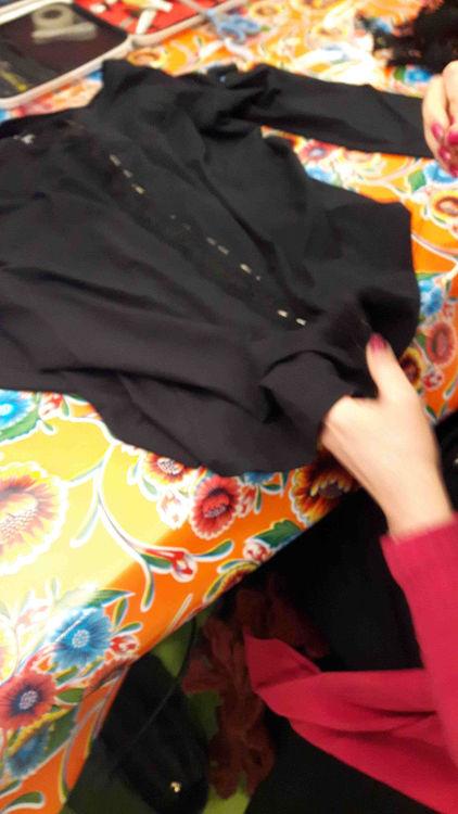 Zoom sur l'ouvrage d'une stagiaire en train de fixer sa dentelle noire de part et d'autre du milieu devant de son T-shirt