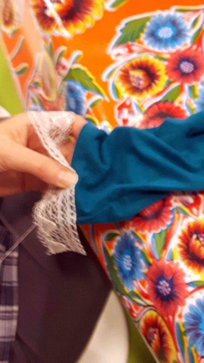 Zoom sur les mains d'une stagiaire en train de fixer sa dentelle blanche au bord de l'extrémité d'une manche bleu canard