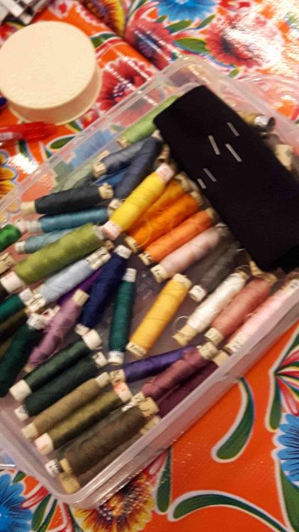 Photo vue du dessus des bobines de fil à broder de toutes les couleurs et aiguilles utilisées pour l'atelier customisation d'un T-shirt avec dentelle