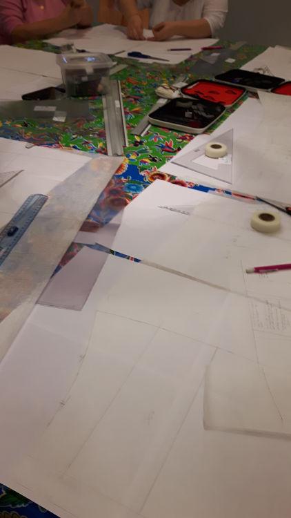 Photo d'un atelier de patronage et transformation de patron prise durant les ateliers du salon Création et Savoir-Faire de 2016 représentant la table de cours avec les patrons des stagiaires en cours de transformation
