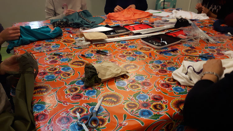 Photo d'un atelier de customisation de T-shirt avec dentelle prise durant les ateliers du salon Création et Savoir-Faire de 2016 représentant la table de cours avec les stagiaires en train de coudre à la main leurs rubans de dentelle Lepuyadentelle.fr