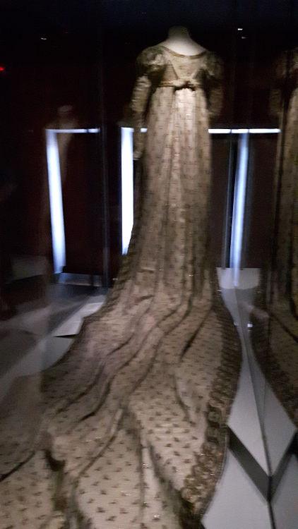 """Robe vue de dos, coloris beige, style empire avec très longue traine brodée de motifs et brodées sur les bord, et ceinture e avec noeud dans le dos - vue à l'exposition """"les robes de Joséphine"""" au musée de la Malmaison (février 2017)"""