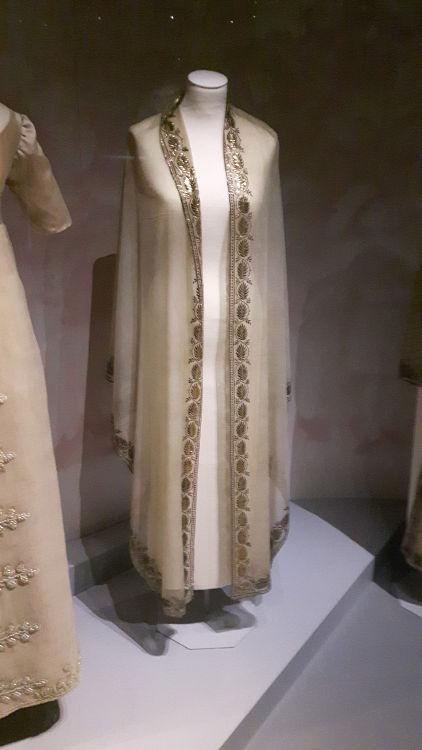 """Manteau vue de face, colori crème, très long, avec broderies dorées larges sur le milieu devant - vue à l'exposition """"les robes de Joséphine"""" au musée de la Malmaison (février 2017)"""