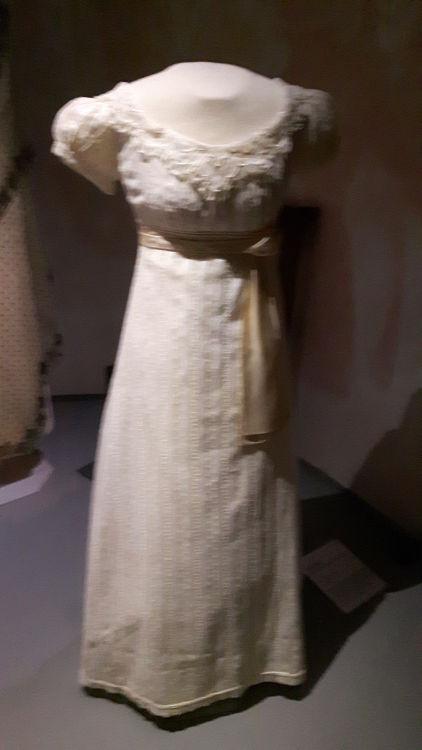 """Robe vue de face, style empire coloris crème avec empiècement de dentelle autour de l'encolure ovale, petites manches ballon, ceinture taille haute et plis nervurés sur le bas de la robe peu ample - vue à l'exposition """"les robes de Joséphine"""" au musée de la Malmaison (février 2017)"""