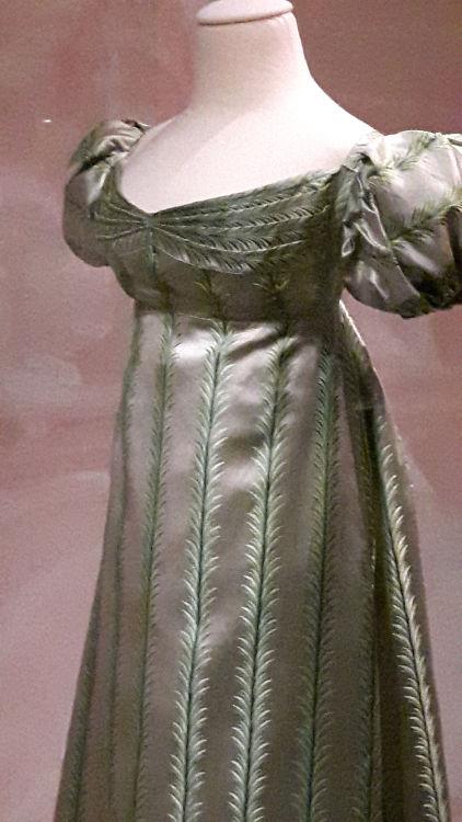 """Robe vue de 3/4 face, style empire en satin vert avec broderies verticales en épis, drapé plissé à la poitrine et manches ballon - vue à l'exposition """"les robes de Joséphine"""" au musée de la Malmaison (février 2017)"""