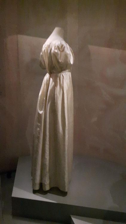 """Robe vue de profil style empire écru avec ceinture taille haute, légère traine et encolure froncée - vue à l'exposition """"les robes de Joséphine"""" au musée de la Malmaison (février 2017)"""