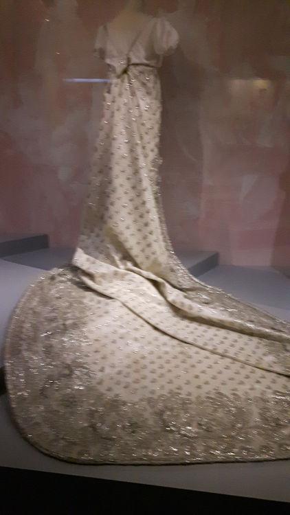 """Robe vue de dos, en tissu type satin intégralement brodé de fil d'argent, grande traine, noeud à la taille - vue à l'exposition """"les robes de Joséphine"""" au musée de la Malmaison (février 2017)"""