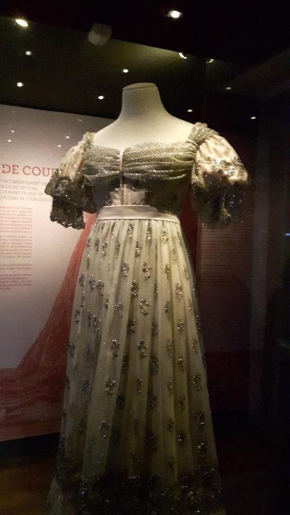 """Robe vue de face, style empire en tissu type mousseline brodée, avec poitrine et épaules drapées, petites manches ballon, taille marquée par une ceinture - vue à l'exposition """"les robes de Joséphine"""" au musée de la Malmaison (février 2017)"""