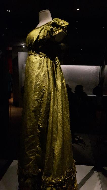 """Robe vue de 3/4, style empire en tissu type taffetas jaune-vert. Modèle à la taille froncée avec les manches ballons - vue à l'exposition """"les robes de Joséphine"""" au musée de la Malmaison (février 2017)"""