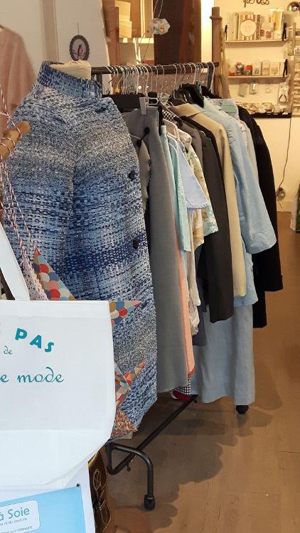 Photo de la salle de cours de Bièvres durant les portes ouvertes de mars 2017 montrant la mise en place : portant avec l'ensemble de modèles exemples présentés, avec au premier plan le manteau style Chanel