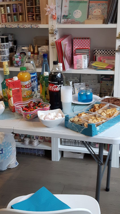 Photo de la salle de cours de Bièvres durant les portes ouvertes de mars 2017 montrant le buffet avec boissons, gâteaux et bonbons, et au fond l'étalage d'articles de loisirs créatifs de la boutique l'Atelier d'Archibald