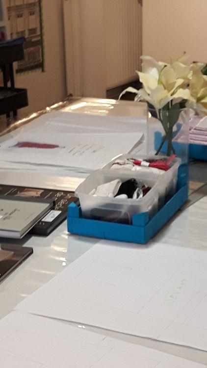 Photo de la salle de cours de Bièvres durant les portes ouvertes de mars 2017 montrant la grande table de cours avec des livres, un bouquet de fleurs, des cagettes turquoise avec des exemples de dentelle, des exemples de patrons