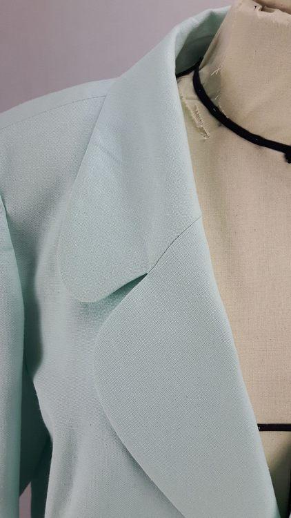 Vue de détail d'une veste en lin coloris vert d'eau avec découpe aux hanches rehaussées de passepoil crème, zoom sur le col tailleur arrondi - modèle exemple des ateliers Rêve à Soie