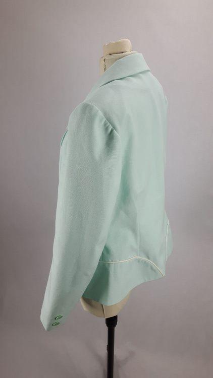 Vue de profil d'une veste en lin coloris vert d'eau avec découpe aux hanches rehaussées de passepoil crème - modèle exemple des ateliers Rêve à Soie