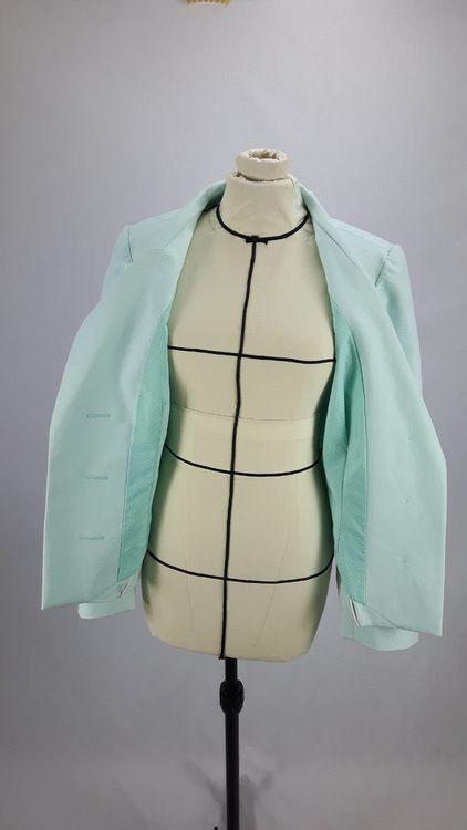 Vue de face d'une veste en lin coloris vert d'eau avec découpe aux hanches rehaussées de passepoil crème, veste ouverte pour laisser apparaître la doublure - modèle exemple des ateliers Rêve à Soie