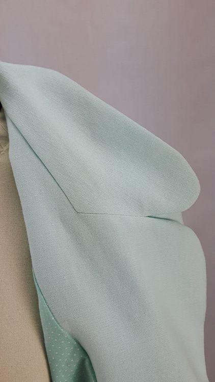 Vue de détail d'une veste en lin coloris vert d'eau avec découpe aux hanches rehaussées de passepoil crème, zoom sur le col tailleur - modèle exemple des ateliers Rêve à Soie