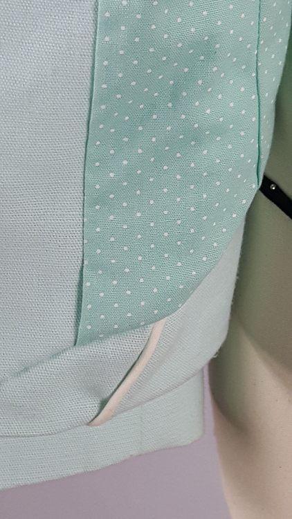 Vue de détail d'une veste en lin coloris vert d'eau avec découpe aux hanches rehaussées de passepoil crème, zoom sur la doublure en coton à pois - modèle exemple des ateliers Rêve à Soie