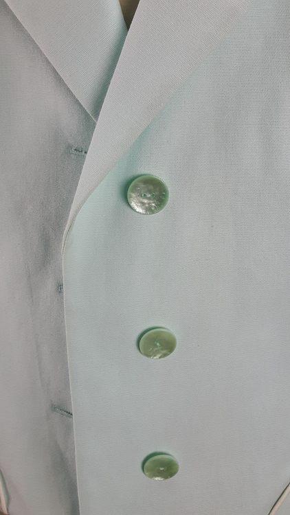 Vue de détail d'une veste en lin coloris vert d'eau avec découpe aux hanches rehaussées de passepoil crème, zoom sur le boutonnage- modèle exemple des ateliers Rêve à Soie
