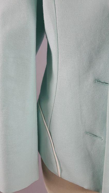 Vue de détail d'une veste en lin coloris vert d'eau avec découpe aux hanches rehaussées de passepoil crème, zoom sur la découpe de hanches- modèle exemple des ateliers Rêve à Soie