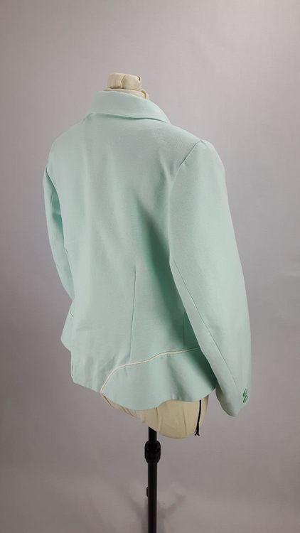 Vue de 3/4 dos d'une veste en lin coloris vert d'eau avec découpe aux hanches rehaussées de passepoil crème - modèle exemple des ateliers Rêve à Soie