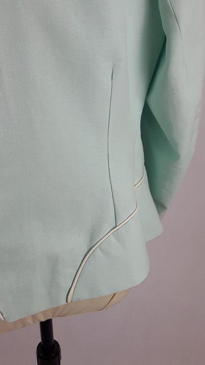 Vue de détail d'une veste en lin coloris vert d'eau avec découpe aux hanches rehaussées de passepoil crème, zoom sur la découpe de hanches vue de dos - modèle exemple des ateliers Rêve à Soie