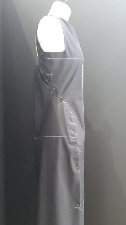Toile noire d'une robe sans manches avec pli cousu sur le côté sur laquelle on distingue les lignes caractéristiques tracée en blanc - vue à l'exposition Balanciaga 2017