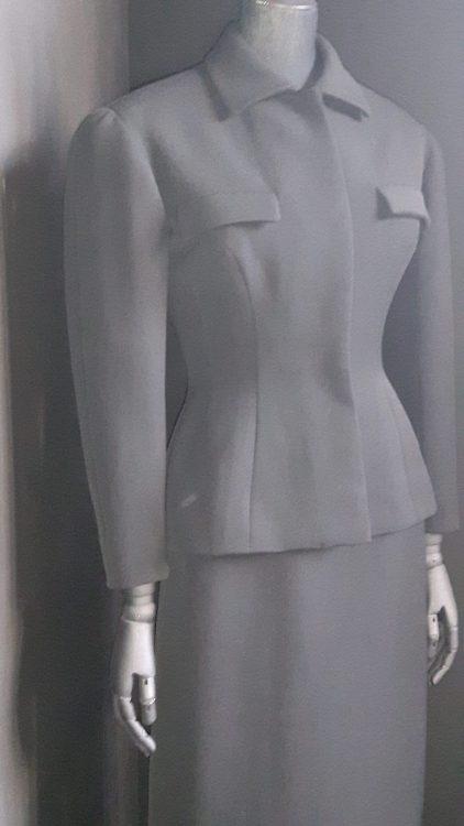 Tailleur noire avec une jupe droite et une veste cintrée avec poches à rabats au-dessus de la poitrine et col chemisier - vue à l'exposition Balanciaga 2017
