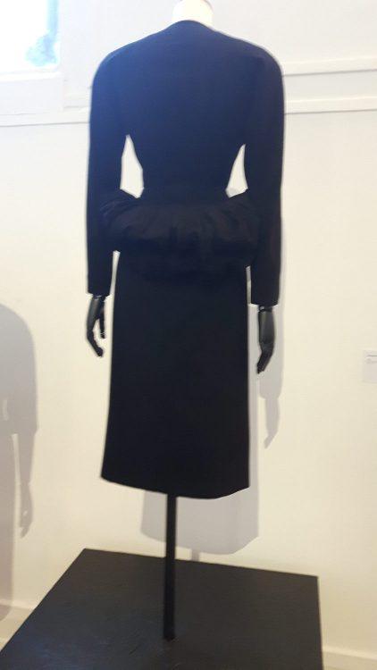 Robe noire à manches longues avec basque volantée dans le dos - vue à l'exposition Balanciaga 2017