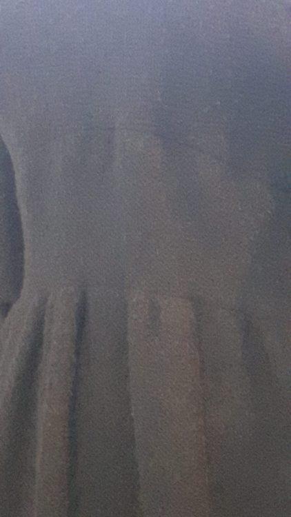 Zoom sur l'empiècement de taille d'une robe noire froncée sur le bas, manches chauve-souris 3/4 - vue à l'exposition Balanciaga 2017
