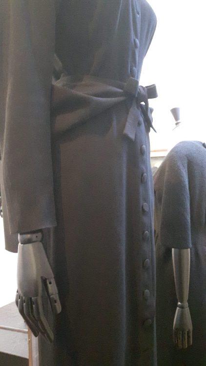 Robe noire manches longues entièrement boutonnée milieu devant avec ceinture drapée nouée - vue à l'exposition Balanciaga 2017
