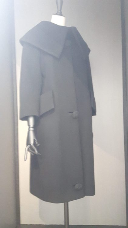 Manteau noir à large col type chemisier tombant sur les épaules, poches à rabat très large - vue à l'exposition Balanciaga 2017