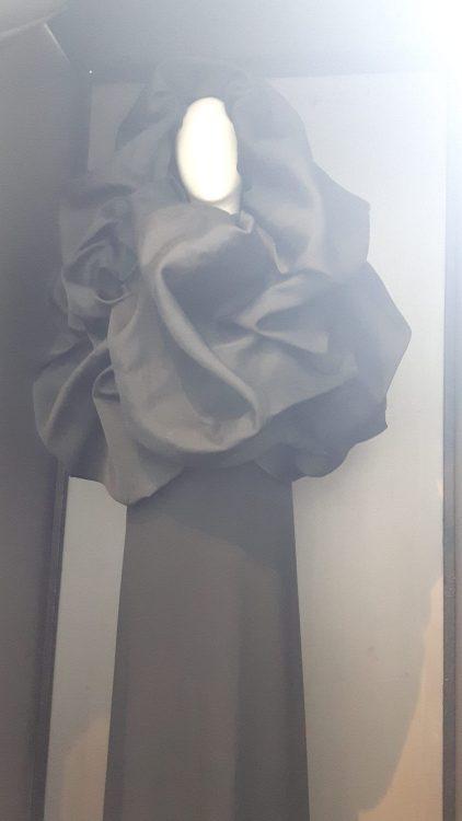 Manteau noir à col-capuche très large volanté - vue à l'exposition Balanciaga 2017