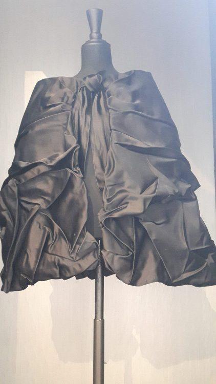 Cape noire forme trapèze avec plissage/fronçage varié sur le devant - vue à l'exposition Balanciaga 2017