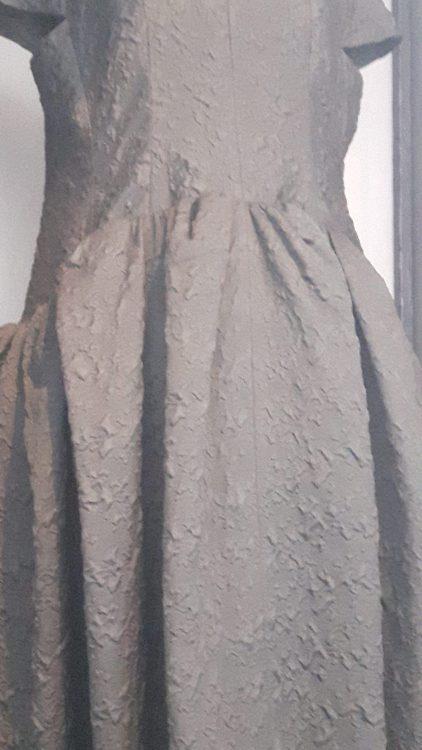 Zoom sur empiècement de taille et froncée sur le bas d'une robe noire avec petits mancherons - vue à l'exposition Balanciaga 2017