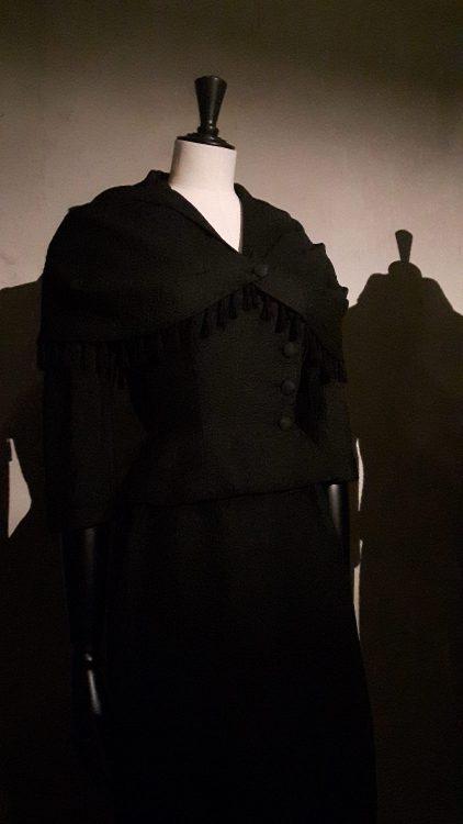 Veste noire à encolure en V avec sur-veste sur les épaule en forme de châle avec bordure à ponpons - vue à l'exposition Balanciaga 2017