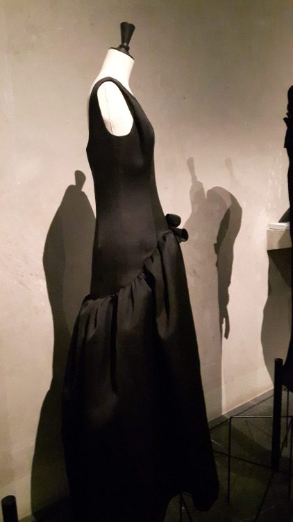 Robe noire avec découpe à la taille devant allant sous les fesses dans le dos, haut de robe ajusté sans manches et bas de robe très froncé - vue à l'exposition Balanciaga 2017