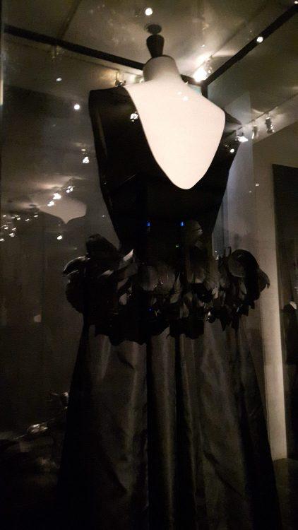 Robe noire sans manches à large décolleté dos et volant à plumes sur les petites hanches - vue à l'exposition Balanciaga 2017