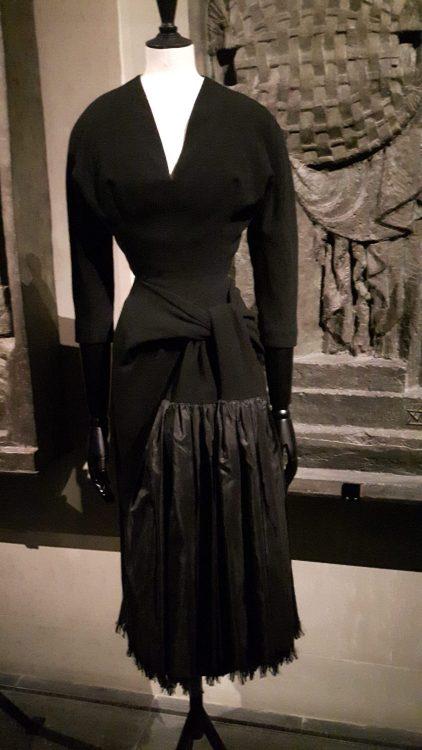 Robe noire avec découpe aux hanches et bas plissé en tissu brillant et haut en tissu mat noué à la taille et encolure profonde en V - vue à l'exposition Balanciaga 2017