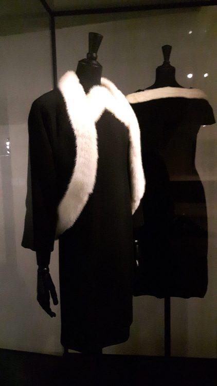 Veste noire ouverte bordée de fourrure blanche à l'encolure et le long du devant, sur une robe avec encolure en pointe bordée de fourrure de même - vue à l'exposition Balanciaga 2017