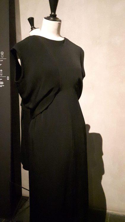 Vue de face d'une robe noire sans manche drapée à la taille sur le devant et froncée sur le bas - vue à l'exposition Balanciaga 2017