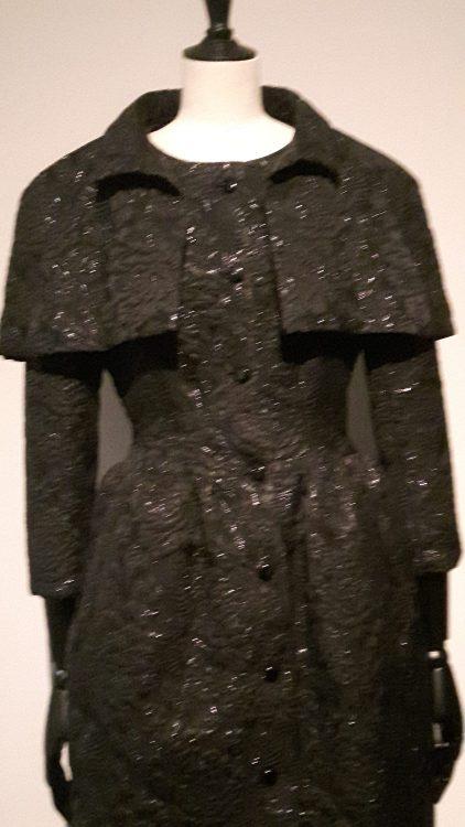 Robe noire superposition d'un haut type boléro sur les épaules et froncée aux hanches, avec encolure ronde et boutonnage devant - vue à l'exposition Balanciaga 2017