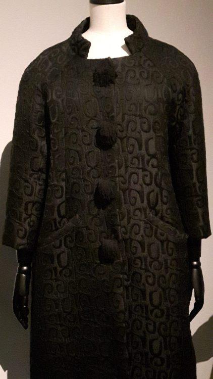 Manteau noir en tissu jacquard avec col montant ouvert, forme droite et boutonnage par gros boutons devant - vue à l'exposition Balanciaga 2017