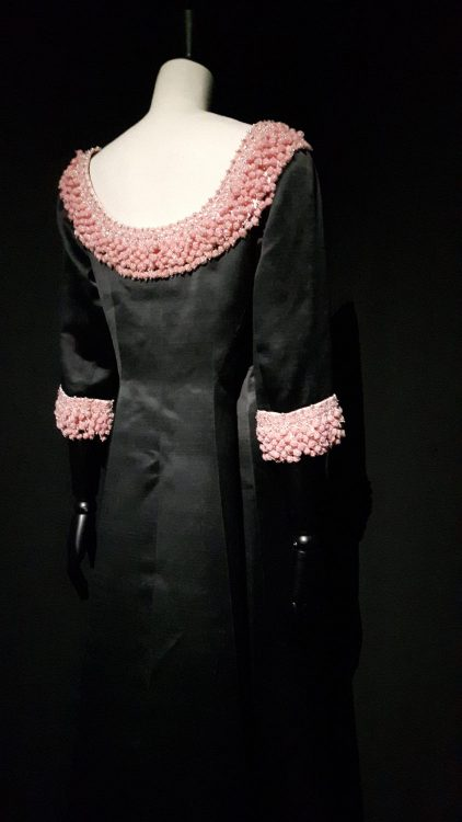 Robe noire avec encolure profonde dans le dos bordée perles couleur corail clair, et manches longues avec perles aussi - vue à l'exposition Balanciaga 2017