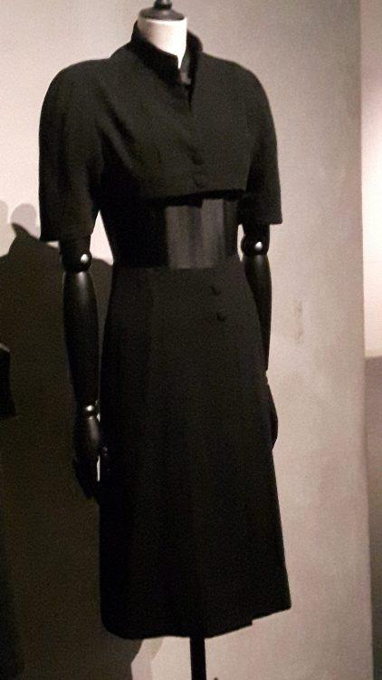 Robe noire droite à manches 1/2 avec forme type boléro sur le haut, col montant et boutonnage milieu devant - vue à l'exposition Balanciaga 2017