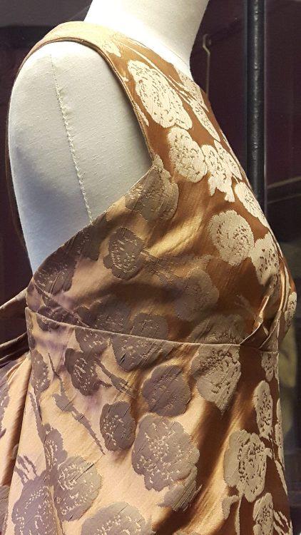 Vue de profil d'une robe en tissu satin rose orangé à bretelle et drapé noués dans le dos - vue à l'exposition Balanciaga 2017