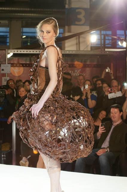 Photo d'une robe présentée au défilé de robe en chocolat du salon du chocolat. Robe avec haut ajusté et bas en sorte de résille ample