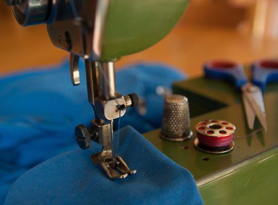 Photo zoom sur le pied de biche d'une machine à coudre en train de piquer dans un tissu bleu avec en arrière plan un dé à coudre, une cannette et une paire de ciseaux