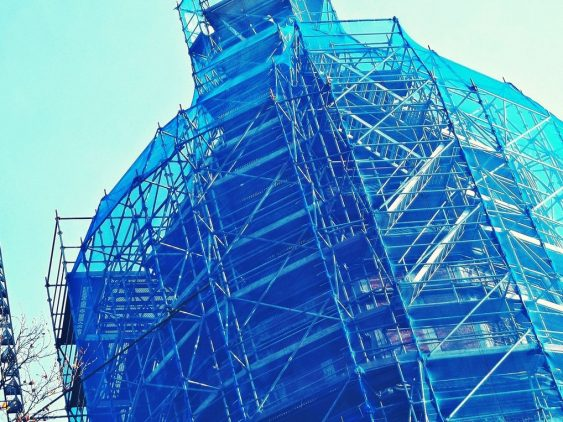 Photo d'un bâtiment type coupole d'église sous échafaudages prise en contre-plongée de teinte bleu turquoise