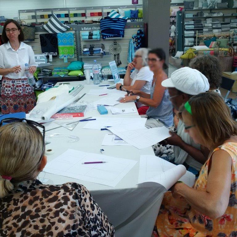 Photo des ateliers-démo Patronage au magasin Tissus des Ursules de Ste-Geneviève-des-Bois : explication d'un exercice de transformation de patron par Christine CHARLES