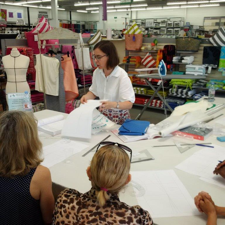 Photo des ateliers-démo Patronage au magasin Tissus des Ursules de Ste-Geneviève-des-Bois : explication d'un exercice de transformation de patron expliqué par Christine CHARLES